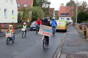 Demoplakat: Fahrradstraßen für Kinder nicht für Blechlawinen. Auf der Straße weiter vorn: Blechlawine